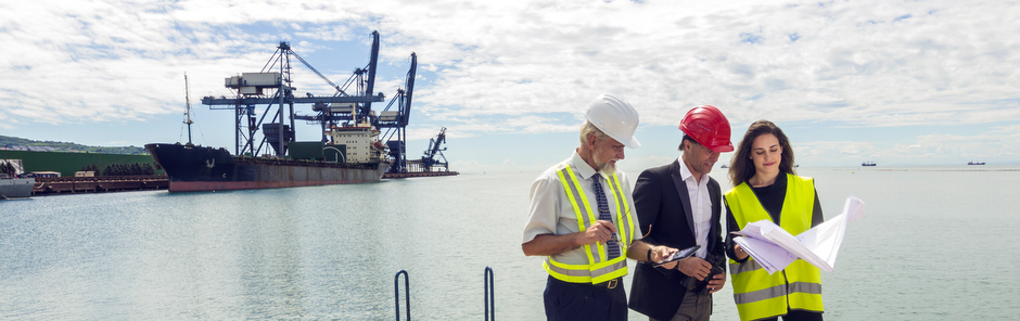 Two men and a woman wearing safety clothing and looking at plans with a large coal shipped docked in the background