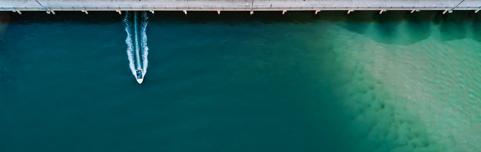 Looking down on a small power boat speeding under a bridge