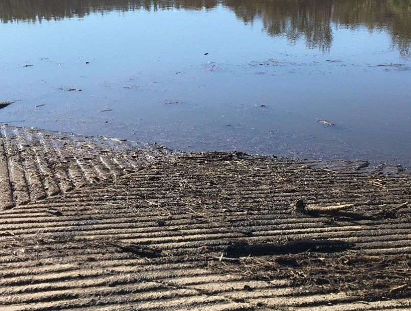 Photo of a boat ramp and the Clyde River after heavy rainfall. There is a lot of ash and sediment on the boatramp and in the water.