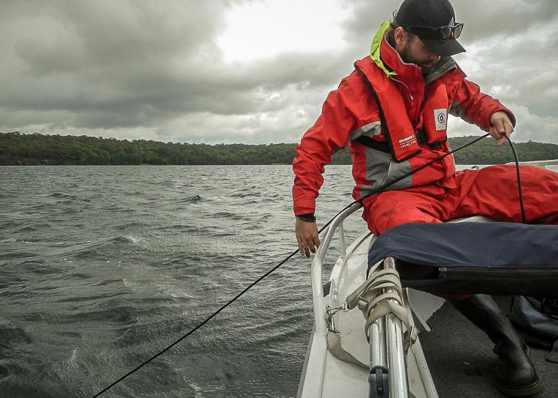 A man wearing wet weather clothing sits on the side of small boat. The boat is on a lake with a wooded hill in the distance. The man is holding an electrical cable for submerged equipment and looking at a monitor.