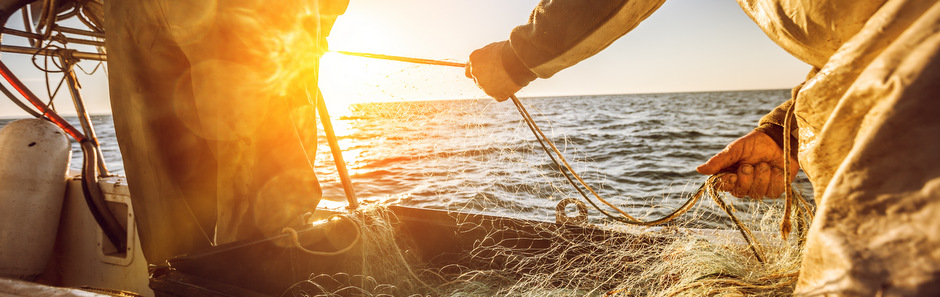 A fishermen is pulling nets back onto a trawler with the sun in the background