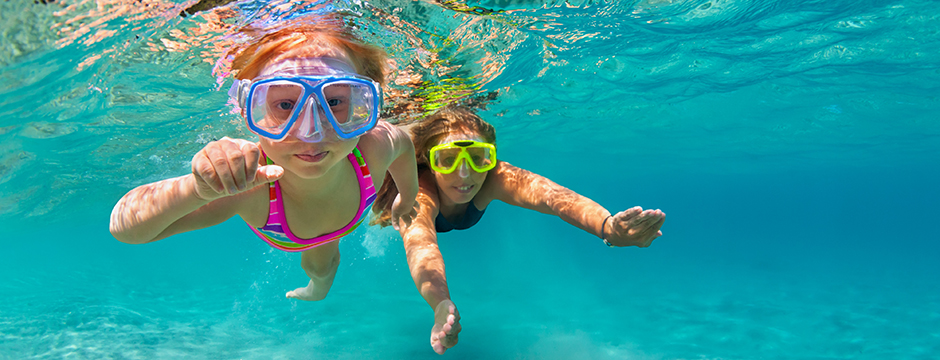 Two girls swimming underwater - Credit: iStock.com - Bicho Raro