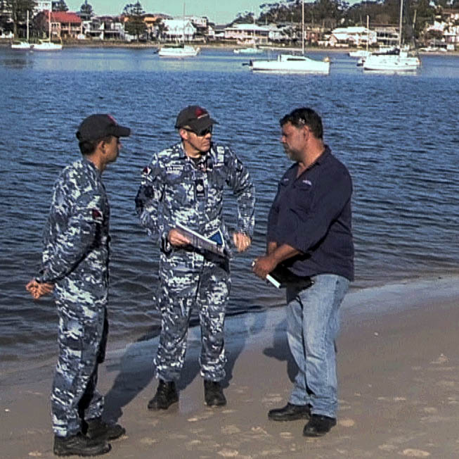 Three men in discussion while standing on a shore
